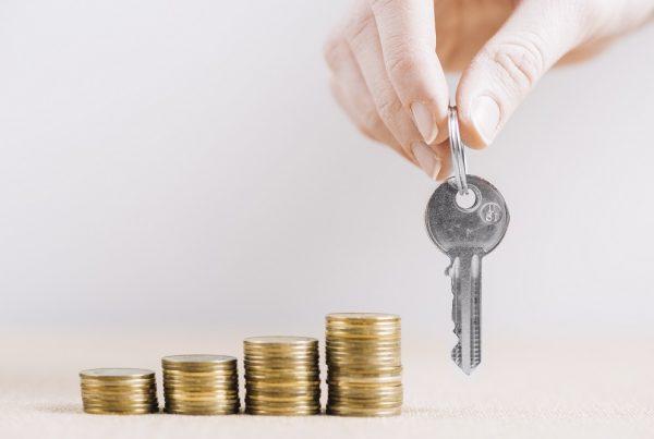 O que valoriza um imóvel - chaves de apartamento e moedas empilhadas
