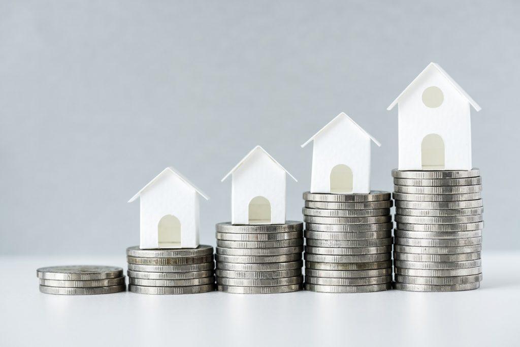 Fatores que influenciam no preço de um imóvel - casinha com moedas