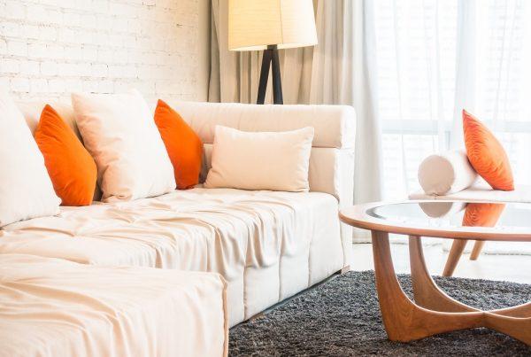Pontos de cor - sofá branco com almofadas laranjas