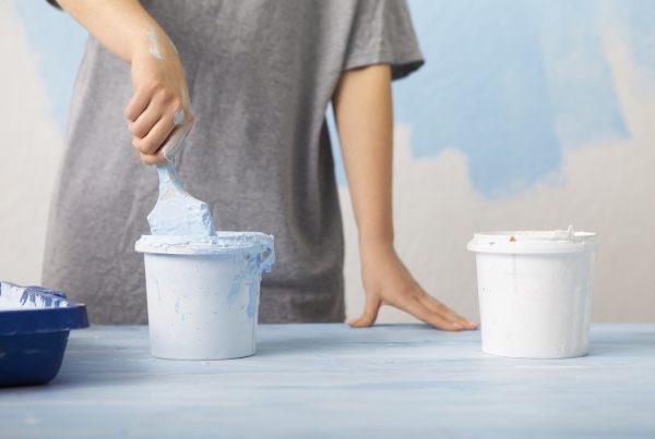 Tipos de tinta - pessoa pintando parede de azul